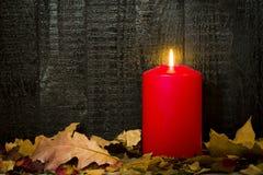 Brennende Kerze mit Blättern auf einem Hintergrund von schwarzen Brettern Lizenzfreies Stockbild