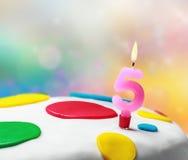 Brennende Kerze mit der Nr. fünf Stockbild