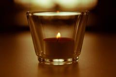 Brennende Kerze mit unscharfem Licht in der Rückseite Lizenzfreie Stockfotos