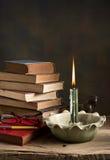 Brennende Kerze und alte Bücher Stockfotos