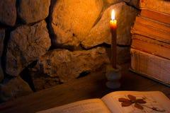 Brennende Kerze und alte Bücher Stockfoto