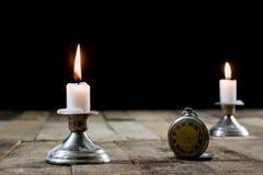 Brennende Kerze und alte Uhr auf einem Holztisch Flüssige Zeit und Lizenzfreie Stockbilder