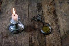 Brennende Kerze und alte Uhr auf einem Holztisch Flüssige Zeit und Lizenzfreies Stockfoto