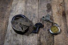 Brennende Kerze und alte Uhr auf einem Holztisch Flüssige Zeit und Stockbild