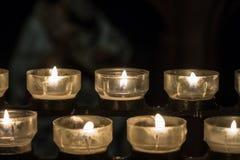 Brennende Kerzen auf einem Kerzenständer in der Kirche Stockfotos