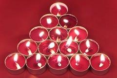 Brennende Kerzen auf Rot stockfoto