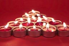 Brennende Kerzen auf Rot stockbilder