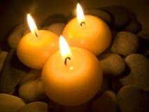 Brennende Kerzen auf Seesteinen Stockfoto