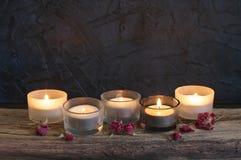 Brennende Kerzen auf verwittertem Holz Stockfotografie