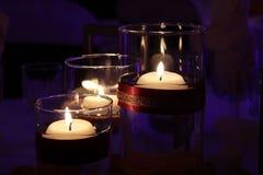 Brennende Kerzen in den Glashaltern mit purpurrotem Hintergrund lizenzfreie stockbilder