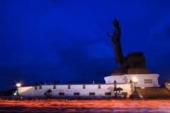 Brennende Kerzen in der Hand um Buddha-Statue Lizenzfreies Stockbild