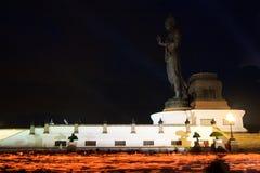 Brennende Kerzen in der Hand um Buddha-Statue Stockfoto
