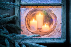 Brennende Kerzen für Weihnachten in gefrorenem Fenster am Vorabend Lizenzfreie Stockfotografie