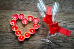 Brennende Kerzen in Form des Herzens mit zwei Flöten Stockfoto
