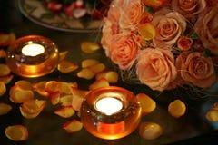 Brennende Kerzen und Blumenblätter stockfotos