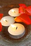 Brennende Kerzen und Blumenblätter in der Schüssel Lizenzfreie Stockfotos