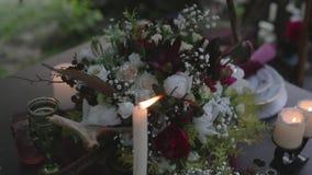 Brennende Kerzen und ein Blumenstrauß von Blumen stock footage