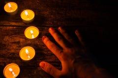 Brennende Kerzen und Hand auf einem hölzernen Lizenzfreie Stockfotografie