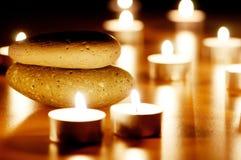 Brennende Kerzen und Kiesel Stockfotos