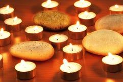 Brennende Kerzen und Kiesel Stockfoto