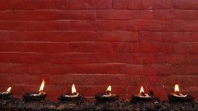 Brennende Lampen gegen Wand des roten Backsteins Reihe des Brennens von Erinnerungslampen auf Hintergrund der hellen roten Wand d stock footage