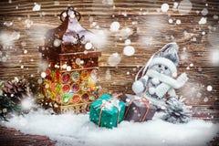 Brennende Laterne und Geschenke im Schnee lizenzfreie stockfotografie