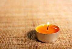 Brennende orange Kerze platziert auf Jutefasermaterial Stockbilder