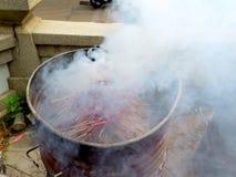 Brennende Räucherstäbchen in einem Stahltank mit weißem Rauche stockfotografie
