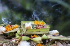 Brennende Räucherstäbchen umgeben mit Balineseangeboten draußen auf einem hindischen Tempel in Ubud, Bali, Indonesien Lizenzfreie Stockfotos