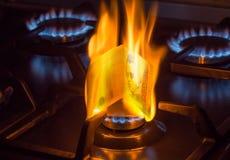 Brennende Rechnung von 100 hryvnias auf einem Gasbrenner, teures Erdgaskonzept stockfotografie