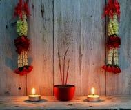 Brennende Räucherstäbchen mit dem Kranz der Blume Einzelne Kerze auf schwarzem Hintergrund Stockfotografie