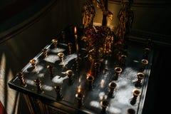 Brennende Wachskerze in der Dunkelheit in der Kirche stockbilder
