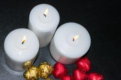 Brennende weiße Kerzen auf einem dunklen Hintergrund Stockfoto