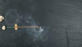 Brennende Weihraucharomastöcke mit Rauche auf schwarzem Hintergrund stockfotografie