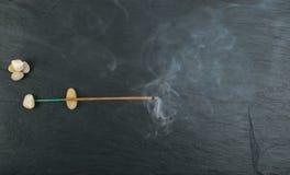Brennende Weihraucharomastöcke mit Rauche auf schwarzem Hintergrund stockbild