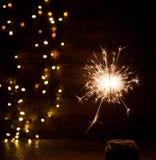 brennende Wunderkerze- und Weihnachtslichter auf hölzernem Hintergrund Stockbilder