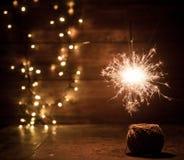 brennende Wunderkerze- und Weihnachtslichter auf hölzernem Hintergrund Lizenzfreies Stockfoto