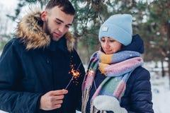 Brennende Wunderkerzen der schönen liebevollen Paare im Winterwaldweihnachten und im Konzept des neuen Jahres lizenzfreie stockfotografie