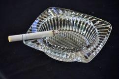 Brennende Zigarette im Aschenbecher Stockfoto