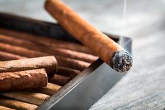 Brennende Zigarre mit Rauche auf hölzernem Luftfeuchtigkeitsregler Stockfoto