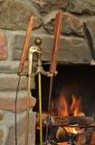 Brennender Kamin mit Eisen-Metallmessingzange und -werkzeugen stockfotos