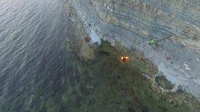 Brennender Koffer fällt von einer Klippe in Schwarzem Meer stock footage