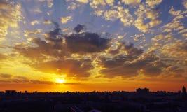 Brennender rötlicher Sonnenaufgang über einer Schlafenstadt Stockbilder