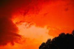 Brennender roter Himmel durch das Sturmbrauen Stockfoto