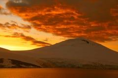 Brennender Sonnenuntergang über eisigem Berg Stockbild
