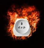 Brennender Stromadapter auf schwarzem Hintergrund Lizenzfreies Stockbild