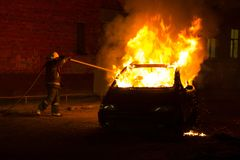 Brennendes Auto auf der Straße in der Nacht Stockfotos
