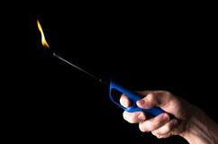 Brennendes Gasfeuerzeug in der Hand eines Mannes Stockbild