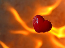 Brennendes Herz mit Flammen gegen Feuerhintergrund Stockfoto