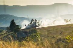Brennendes Heu des Herbstes auf einem Gebiet, ein Bauernhof in den Bergen Stockfotos